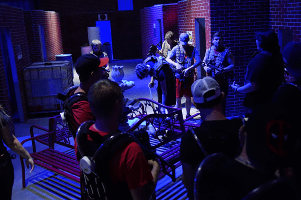Adults and Teens strategizing on the laser tag battlefield