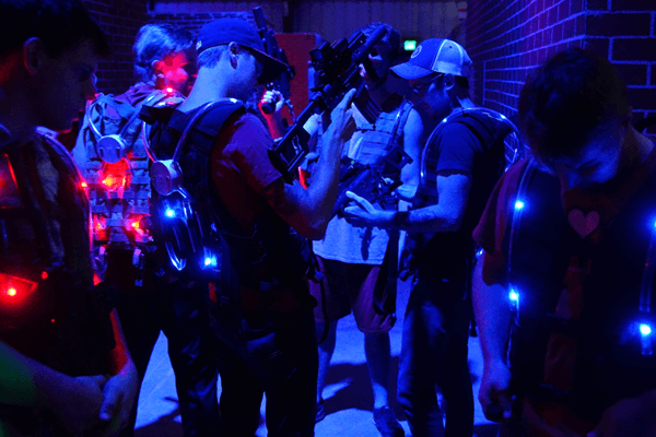 Team gears up with laser tagger and vest before combat
